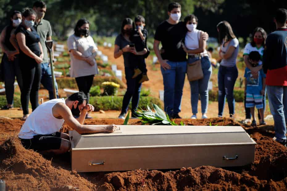 A family says goodbye to a relative during a funeral in the Vila Formosa cemetery, in Sao Paulo, Brazil, on Wednesday.