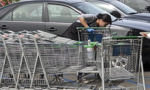 A worker sanitizes shopping carts at a Whole Foods in Los Angeles.
