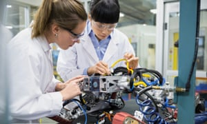 Female engineers assembling robotics in factory