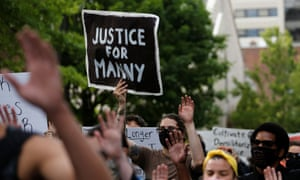 A protester holds a 'Justice for Manny' sign during a march following the death of Manuel Ellis in Tacoma, Washington, on 5 June.