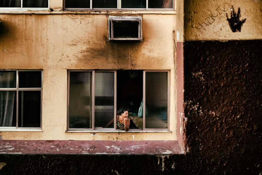 A woman at a window of her apartment in Cruzada Sao Sebastiao, in Leblon