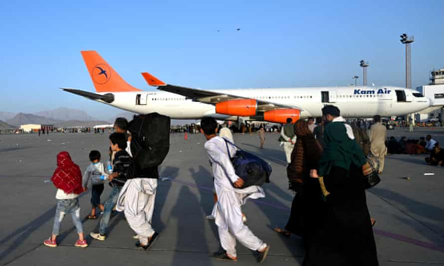 Afghan families walk by the aircrafts at the Kabul airport