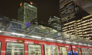 A DLR train pulls in at Canary Wharf at night