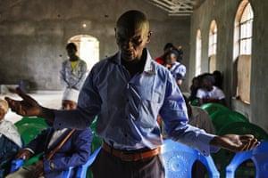 Muchara Ntiba's son prays at a church in the Kenyan highlands