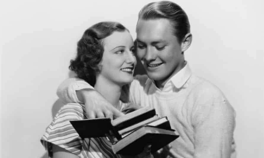photo of two people embracing while holding some books
