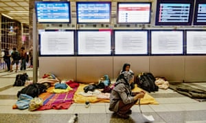Stranded people at Vienna's train station after train services to Germany were suspended.