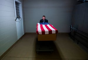 Brandon Cochran, a crematory operator, pushes a cremation box draped in a US national flag, containing the body of a veteran who died of coronavirus.
