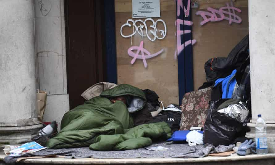 A homeless man sleeps in the doorway of a closed branch of the Leeds building society in Holborn, London