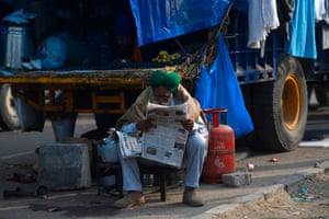 A farmer reads the news on a road blocked by police to stop farmers from marching to New Delhi, at the Delhi-Haryana state border in Kundli. Behind concertina wire and trucks blockading a major highway into the capital, thousands of farmers are camping out in the bitter winter cold as they protest against agriculture reforms they fear could destroy their livelihoods.