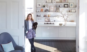 Meredithe Stuart-Smith leaning against the doorway to the kitchen, white shelving with pictures on behind and Lulu the dog under her arm