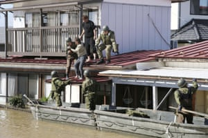 Local residents are rescued by Japanese Defence-Force soldiers from a flooded area in Kakuda, Miyagi prefecture.