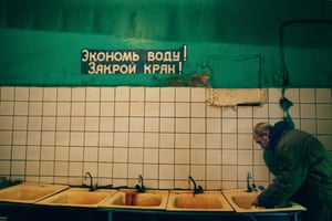 An inmate washes his hands before dinner, under the sign 'Save the water, close the tap'