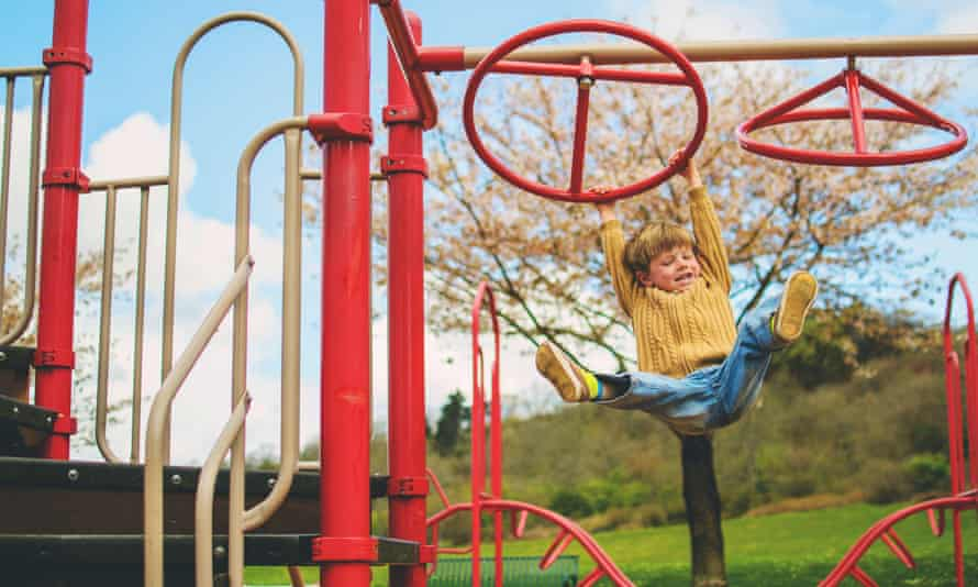 Happy boy hanging on a climbing frame in a garden