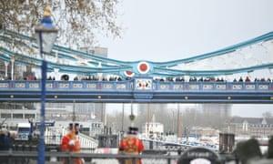 Spectators watch the gun salute from Tower Bridge.
