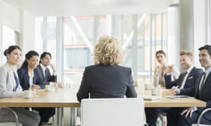 Woman sitting at head of board meeting