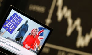 A TV screen is seen next to the German share prize index DAX board at the stock exchange in Frankfurt, Germany