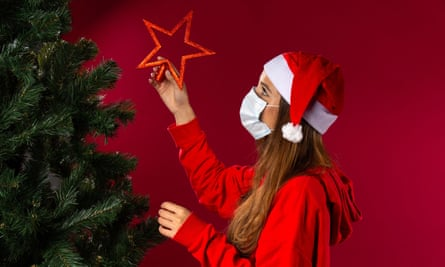 A woman in face mask put decorations on a Christmas tree.