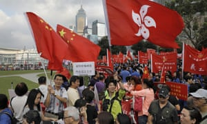 In Hong Kong thousands of pro-Beijing protesters raise Chinese and Hong Kong flags during a rally outside government headquarters on Sunday.