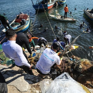 Volunteers clean up Port of Gaza from waste materials in Gaza City.