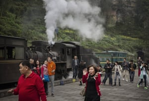 Chinese tourists react as a coal powered engine lets off steam at the station in the former mining town of Bagou