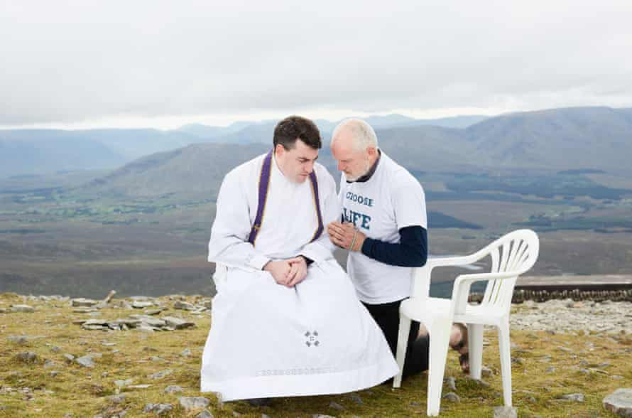 An anti-abortion campaigner recites the Eucharist with a priest at the summit of Croagh Patrick, a holy mountain in County Mayo, on 26 August 2017.