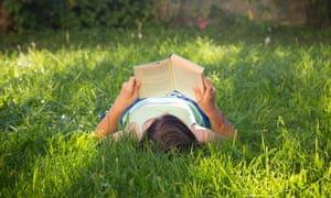 Girl reading book while laying on grass