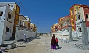 People walk through Daru Salaam city, a new housing estate in northern Mogadishu.