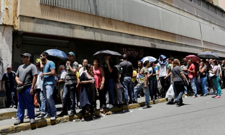 People queue to buy basic food items outside a supermarket in Caracas.