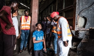 Abdul Raouf Akinwoye, a retired police officer who works with the Nigerian Railway Corporation, forces a squatter to kneel in front of him. Meanwhile, on the other side of the train carriage, artists were putting up their works.