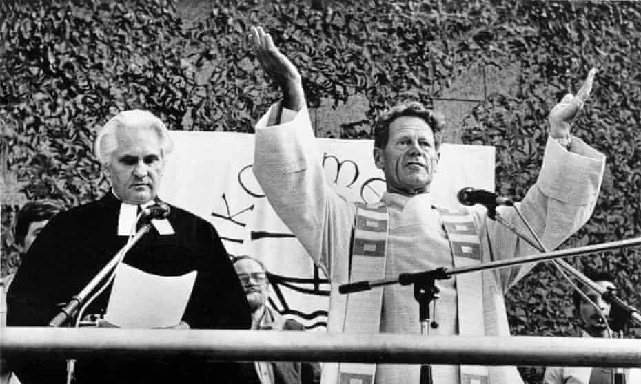 Hans Kung in priest's robes, both arms upraised, with a banner of the ecumenical movement visible behind and another priest standing next to him