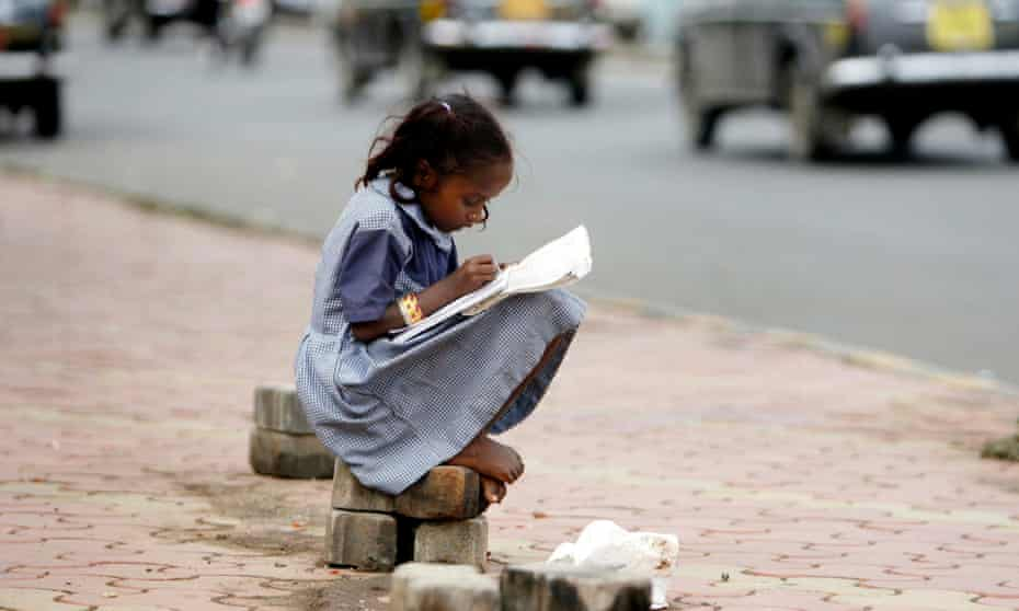 In this 2007 image, Nusrat, a girl belonging to a homeless family, studies school books at pavement in Mumbai