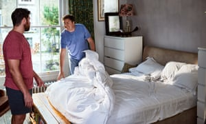 Men changing their bedsheets together.