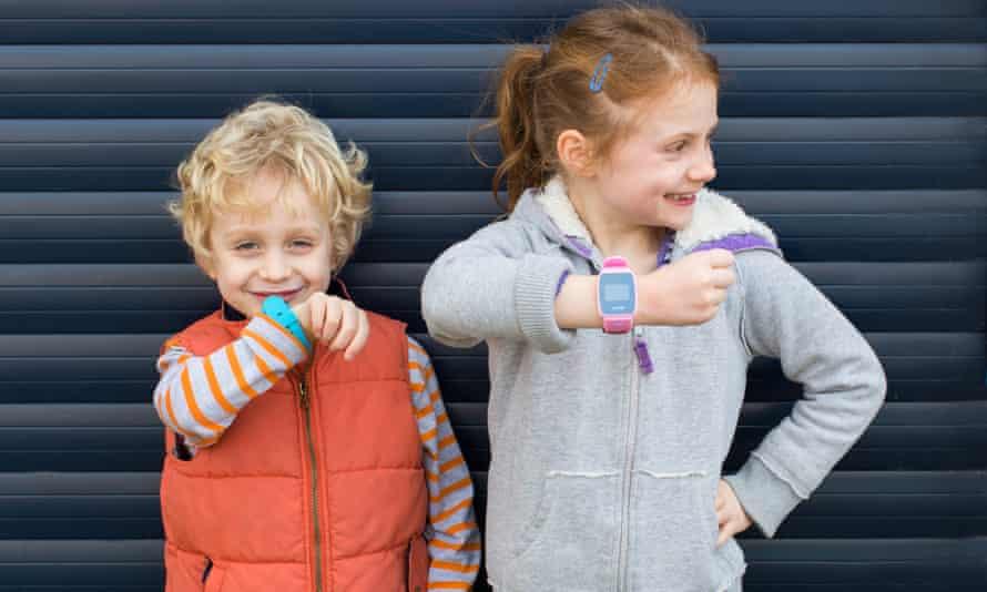 Two children wear the Gator Watch device