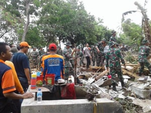 Indonesian aid personnel work to recover victims and help survivors after the Sunda Strait tsunami.