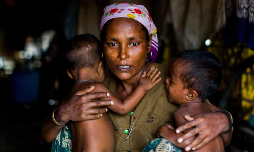 A mother – in a camp for Rohingya in Sittwe – Myanmar, holds onto her twins, both of whom suffer from malnutrition.