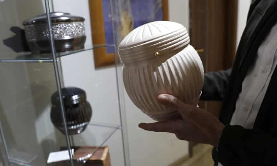A man chooses an urn at a funeral parlour in Rome.