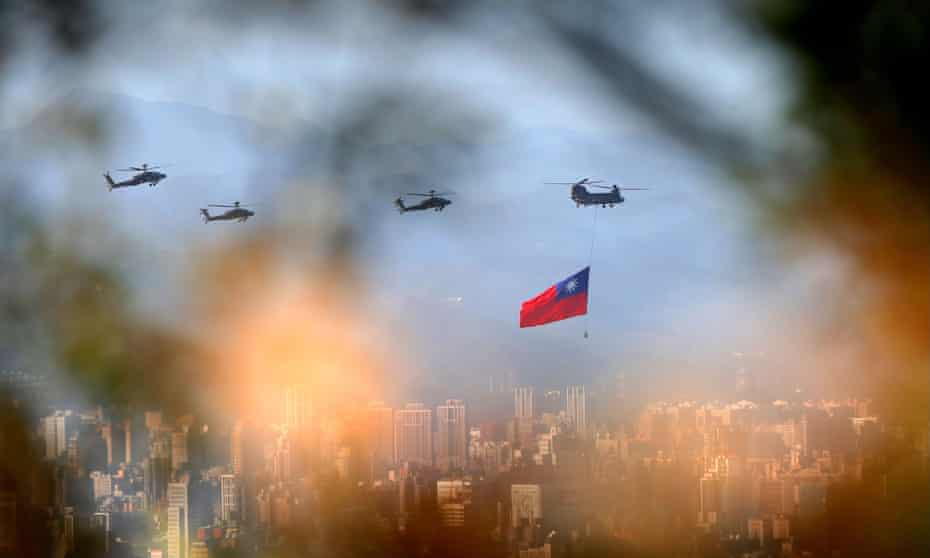 Military helicopters, one trailing a Taiwan flag, rehearse for Taiwanese national day celebrations.