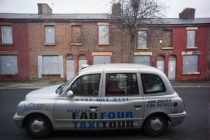 A taxi parked in front of the boarded-up former home of Ringo Starr in Madryn Street