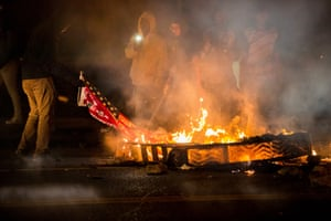 A protester burns as protests over the killing of an 18-year black man by St. Louis police turned violent.