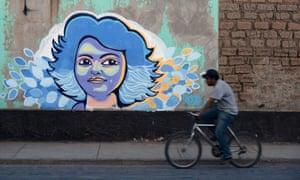 A man cycles past graffiti of Berta Cáceres in La Esperanza