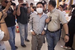 Boonchai Bach (C), 40, an alleged kingpin in Asia's illegal trade in endangered species is escorted past journalists at a police station in Bangkok, Thailand