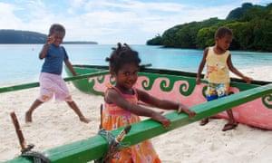 Children play on Champagne beach, Espiritu Santo, Vanuatu.