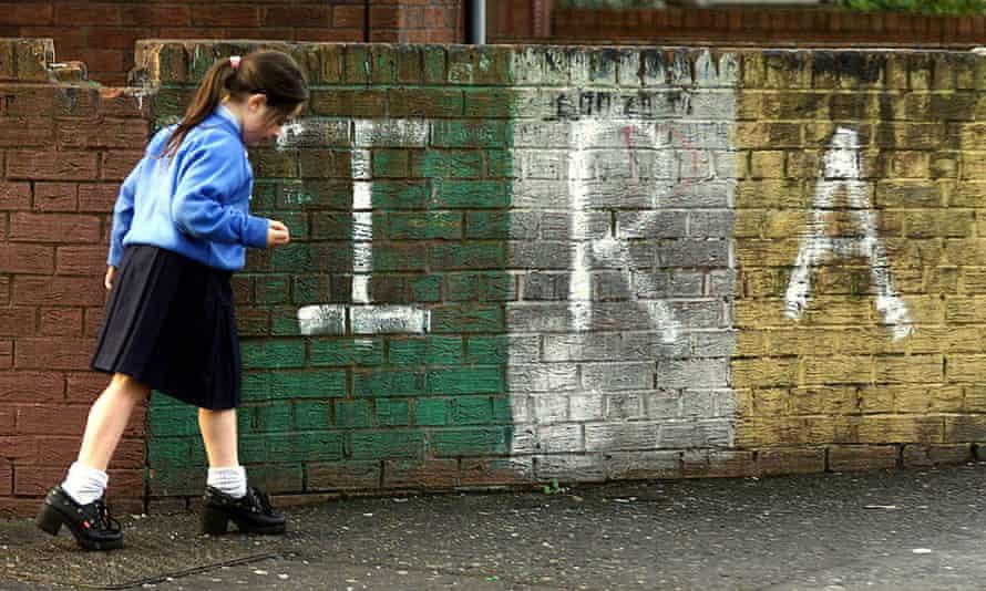 A schoolgirl walks past IRA graffiti in the Newlodge area of north Belfast in November 1999