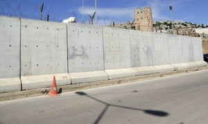 FILE - This May 24, 2017 file photo shows the newly built wall near Cilvegozu border gate in Reyhanli, at the Turkey-Syria border. Turkish President Recep Tayyip Erdogan says his country plans to build walls along its borders with Iraq and Iran, similar to the one currently being erected along the frontier with Syria. Erdogan said late Thursday June 1, 2017 that Turkey has so far completed the construction of a 650-kilometer (403-mile) stretch of the wall along the 911-kilometer border with Syria.(AP Photo/Burhan Ozbilici, File)