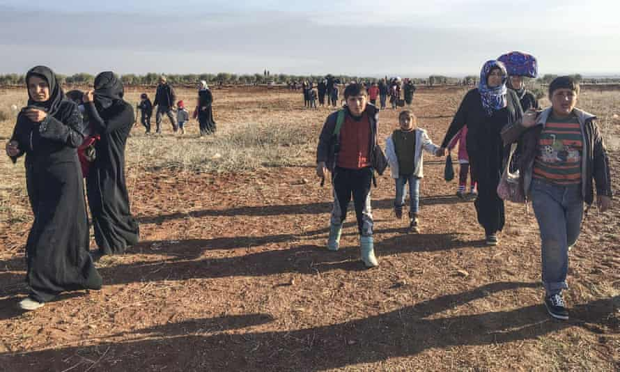 tired looking Syrian women and children walk across a field
