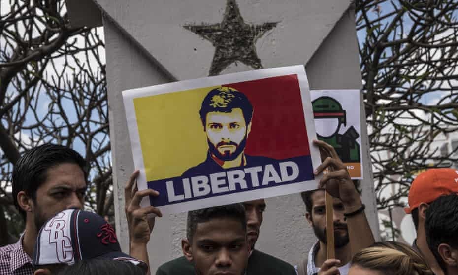 A man holds a poster of the opposition leader Leopoldo López, who is under house arrest, during a protest in Caracas on 30 January 2019.