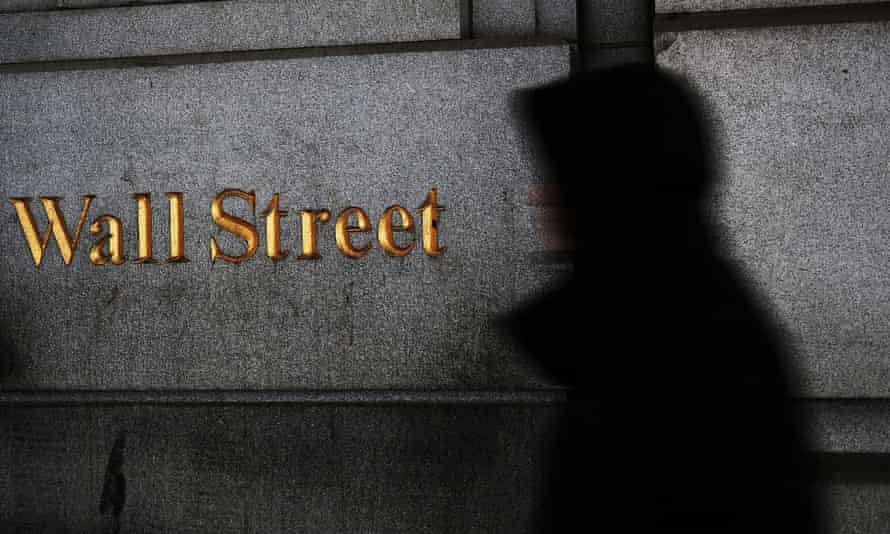 A person walks past the New York Stock Exchange with a sign saying Wall Street in gold