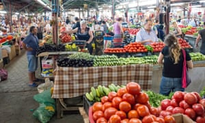 Stalls in indoor Green Market, Kutaisi, a pile of tomatoes in the foreground