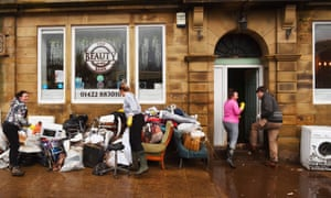 Mytholmroyd, UK. People clear up at a business after flooding brought by Storm Ciara