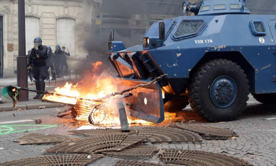 A Gendarmerie armored vehicles (VBRG) drives past fire near the Champs Elysees avenue in Paris on December 8, 2018